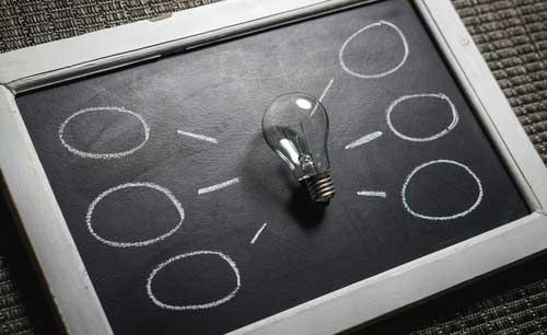 Tableau avec une ampoule et des bulles qui représente la communication en entreprise
